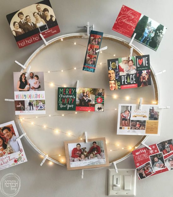 What a smart idea! Use an old embroidery hoop to create a DIY Christmas card holder, complete with copper wire fairy lights.